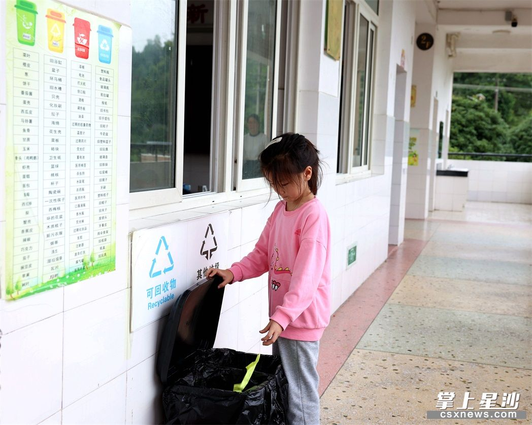 江背镇印山学校每个教室门口均设置了分类垃圾桶,学生按图表正确投放。