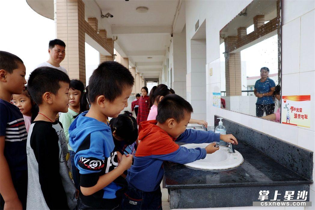 今年,江背镇印山学校更换了一批节水龙头。图为学生有序排队洗手。