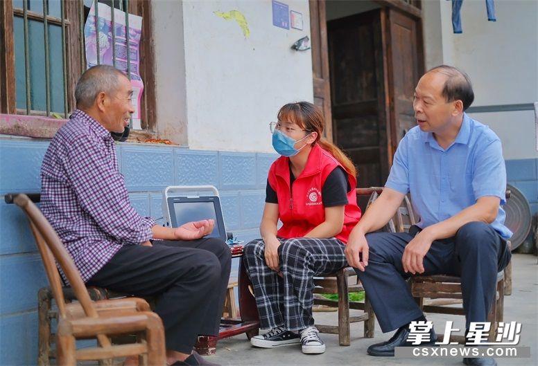 金江新村驻村工作队队长陈长辉、家庭医生吴姝洁在贫困户张再益家中做健康随访。 章帝 摄