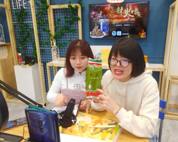 图为湖南信息学院学生与当地村民一起作为新农主播,为网友介绍金井绿茶。